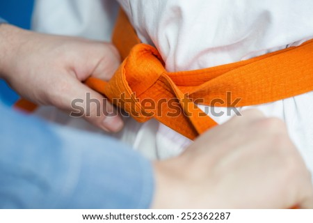 A father ties an orange belt on his son's uniform for martial arts - stock photo