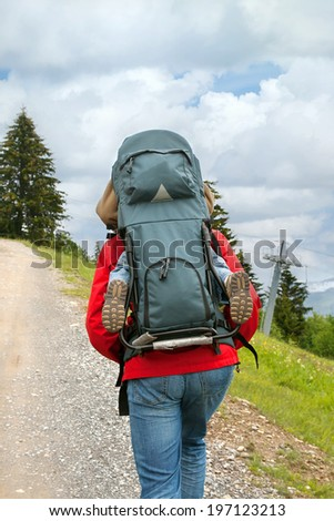 a father with a child in a backpack is in the mountains - stock photo