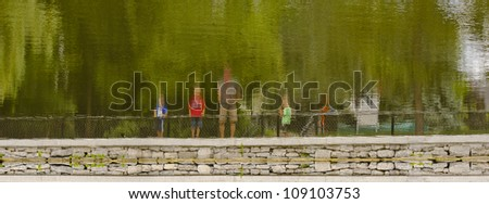 A father with his sons out fishing reflection in the water on the Rideau canal in Ottawa, Canada. - stock photo