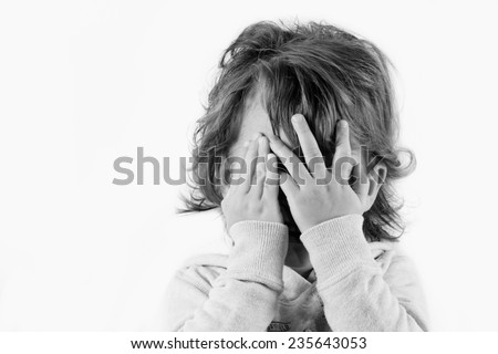 A fearful child in black and white isolated on white background - stock photo