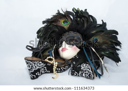 A feathered porcelain mask, sandals, and pearls. - stock photo