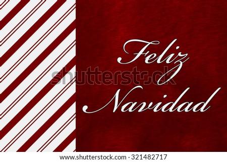 A Feliz Navidad - Merry Christmas card, A Candy Cane Stripes with words Feliz Navidad over red plush background - stock photo