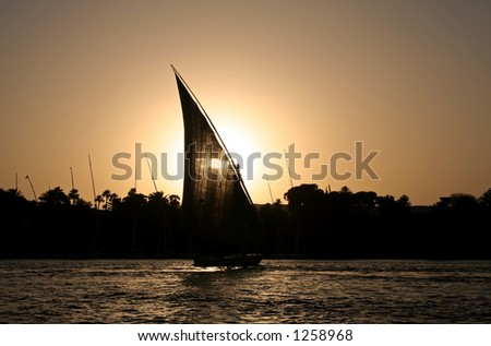 A felucca sailing at the Nile River during sunset time - stock photo