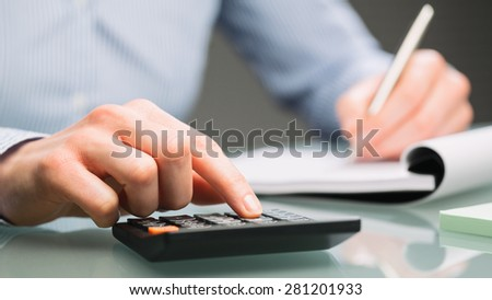 A female accountant uses a calculator and takes notes on a paper notebook on an office desk. - stock photo