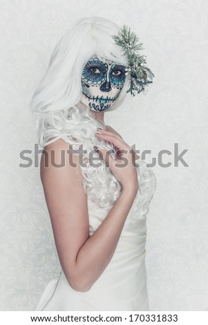 a female bride with her face painted as a traditional day of the dead sugarskull mask - stock photo
