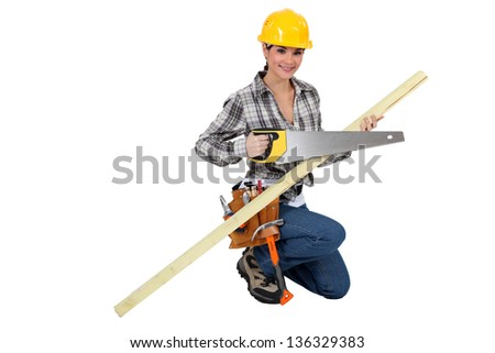 A female carpenter with a handsaw. - stock photo