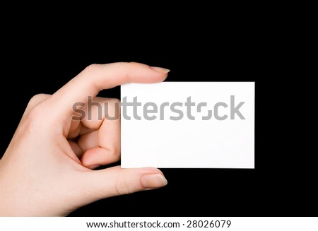 A female Caucasian hand holding a blank white business card between her fingers. Image isolated on black studio background. - stock photo