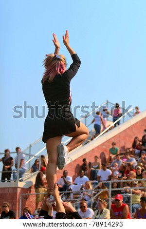 A female cheerleader leads the crowd at a football game.  Copy space across top. - stock photo