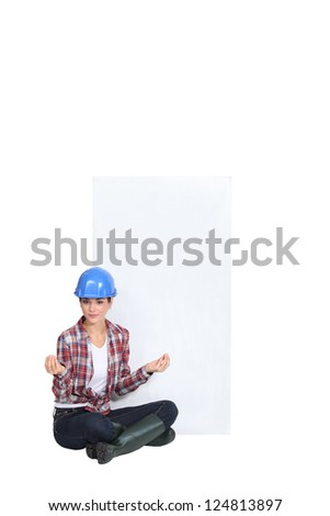 A female construction worker in the lotus position. - stock photo