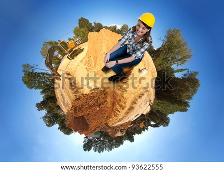 A Female Construction Worker on a job site wearing a hard hat - stock photo