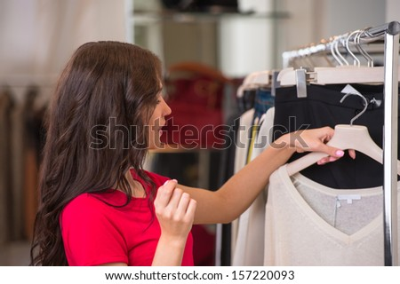 A female consumer shopping in an clothes store with joy and expression - stock photo