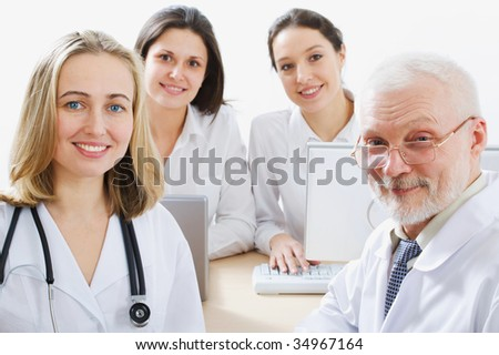 A female doctor stays in front of her team - stock photo