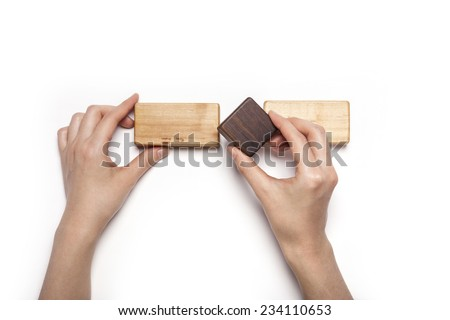A female hand hold(pick up) the walnut wood block among the various wood blocks isolated white, top view at the studio. - stock photo