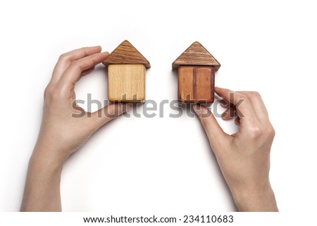A female hand hold(pick up) the wood block among the wood blocks like two house(real estate) isolated white, top view at the studio. - stock photo