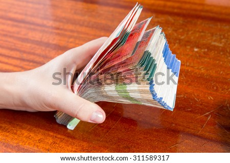 A female hand holding two hundred shekel bank notes against wood background. Concept photo of money, banking ,currency and foreign exchange rates. - stock photo