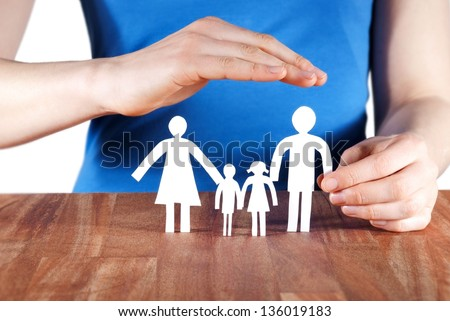 a female hand protecting a paper chain family - stock photo