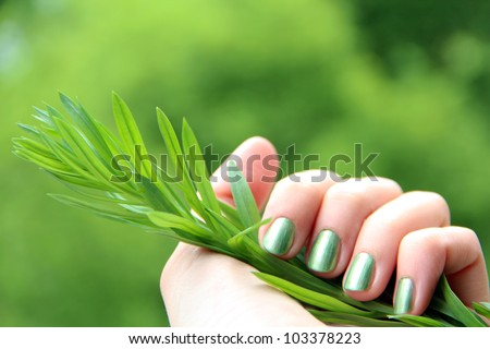 A female hand with spring green (mint coloured) nail polish on holding a twig against a green background - eco-friendly nail polish - stock photo