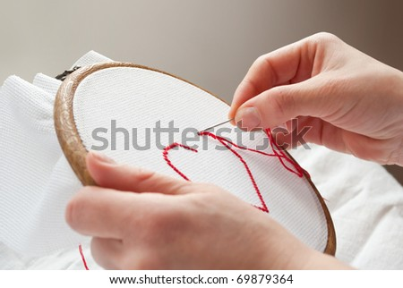 a female hands embroidering red heart - stock photo