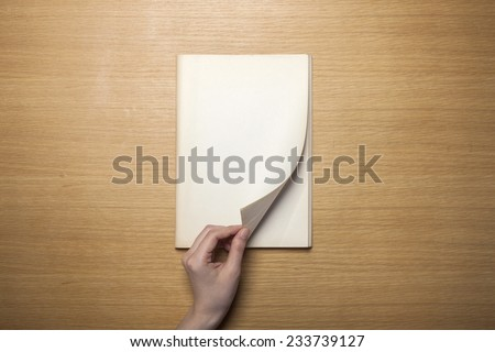 A female hands hold(grip) a vintage(old) book(note, diary) spread through the pages of a book on the wooden desk with pencil, top view at the studio. - stock photo