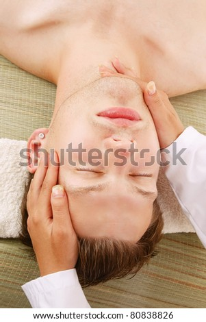 A female hands massaging  man's face in a spa center - stock photo