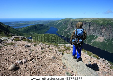 A female hiker standing on Gros Morne Mountain above Ten Mile Pond in Gros Morne National Park, Newfoundland, Canada. - stock photo