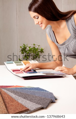 A female interior designer looking at rug samples from a catalogue - stock photo