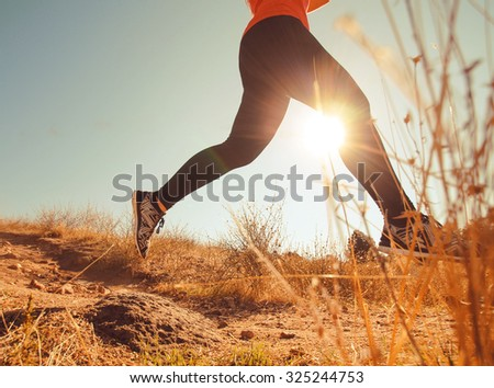a female jogger sprinting down a grassy hill during sunrise or sunset on the hills above a city toned with a retro vintage instagram filter app or action effect - healthy jogging or running concept  - stock photo