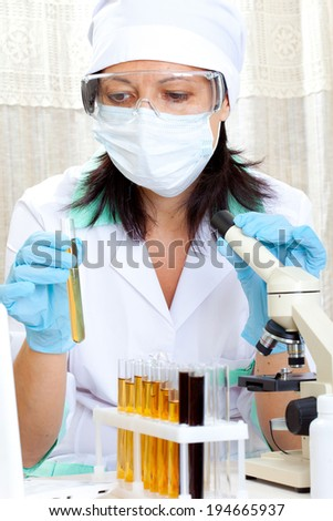 a female medical or scientific researcher or woman doctor looking at a test tube of yellow solution in a laboratory - stock photo