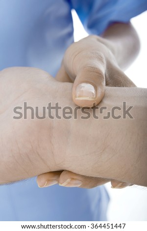 A female nurse is checking her patience's blood pressure. Isolated on white background. - stock photo