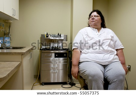 A female patient waiting in a doctors office - stock photo