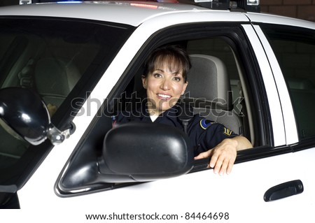 a female police officer sitting in her patrol car during a night shift. - stock photo