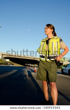 A female police officer staring and looking serious during a traffic control shift. - stock photo