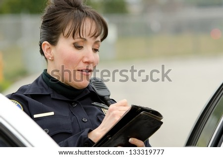 a female police officer writes a ticket while standing next to her patrol car. - stock photo