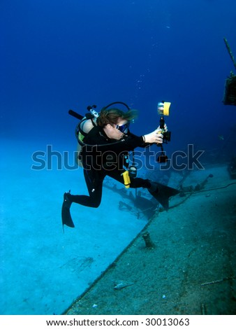 A Female Professional Underwater Photographer shooting the MV Tibbetts in Cayman Brac - stock photo