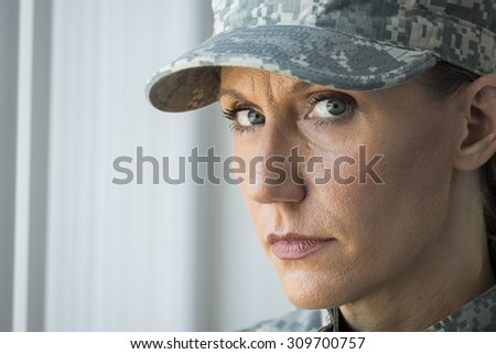 A female soldier looking at the camera, blank stare - stock photo