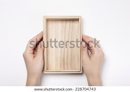 A female(woman, girl) two hands hold a empty wooden box isolated white, top view. - stock photo