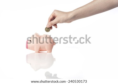 A female(woman) hand hold a coin into the pig coin bank(money box) isolated white at the studio. - stock photo