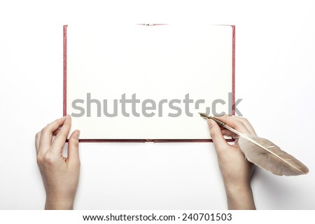 A female(woman) hand hold a feather quill pen on the empty(blank) book(diary, sketchbook, note)isolated white at the studio. - stock photo