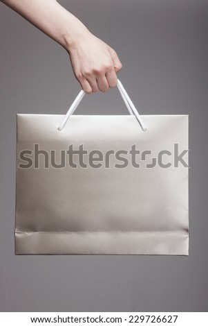 A female(woman) hand hold a gold shopping bag(paper bag) and white strings at the studio. - stock photo