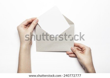 A female(woman) hand hold a letter with envelope isolated white at the studio. - stock photo