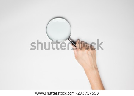 A female(woman) hand hold a magnifier(reading glass) isolated white at the studio. on white background - stock photo