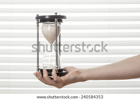 A female(woman) hand hold a sand timer(hourglass) at the white blind background and table(desk). - stock photo