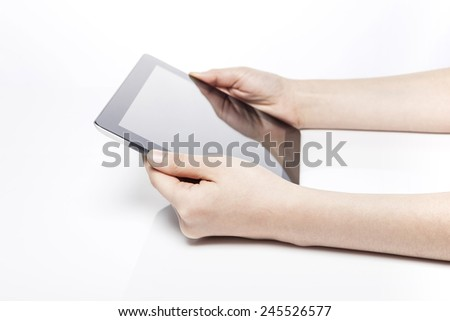 A female(woman) hand hold(touch) a tablet on the desk isolated white at the studio. - stock photo