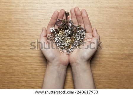 A female(woman) hand hold various vintage keys on the wood office desk(table) top view at the studio. - stock photo