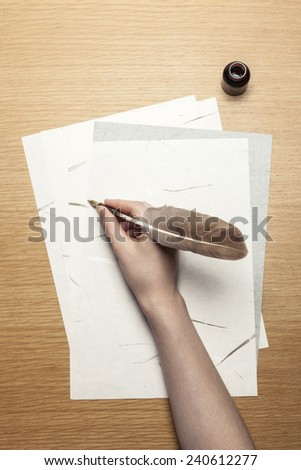A female(woman) hand hold(write) a feather quill pen with ink on the letter paper and wood desk(table), top view at the studio. - stock photo