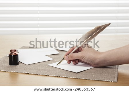 A female(woman) hand hold(write) a vintage feather quill pen with envelope and letter, ink on the office desk(table) behind white blind - stock photo