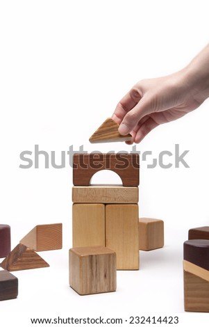 A female(woman) hand pick up(hold, make) the house(building) with wood blocks symbolizing real estimate isolated white at the studio. - stock photo