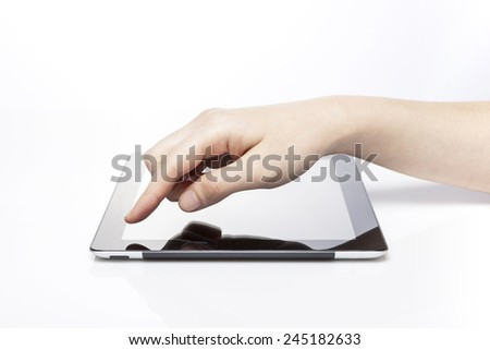 A female(woman) hand touch the empty(blank) tablet pc screen isolated white at the studio. - stock photo