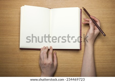 A female(woman) hands hold a blank(empty) book(note, diary) with pencil on the wood desk(table), top view at the studio. - stock photo