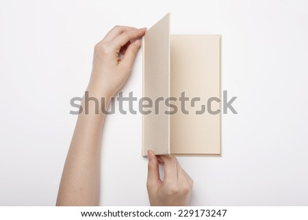 A female(woman) two hands hold(spread, unfold) a book(diary, note) isolated white, top view. - stock photo